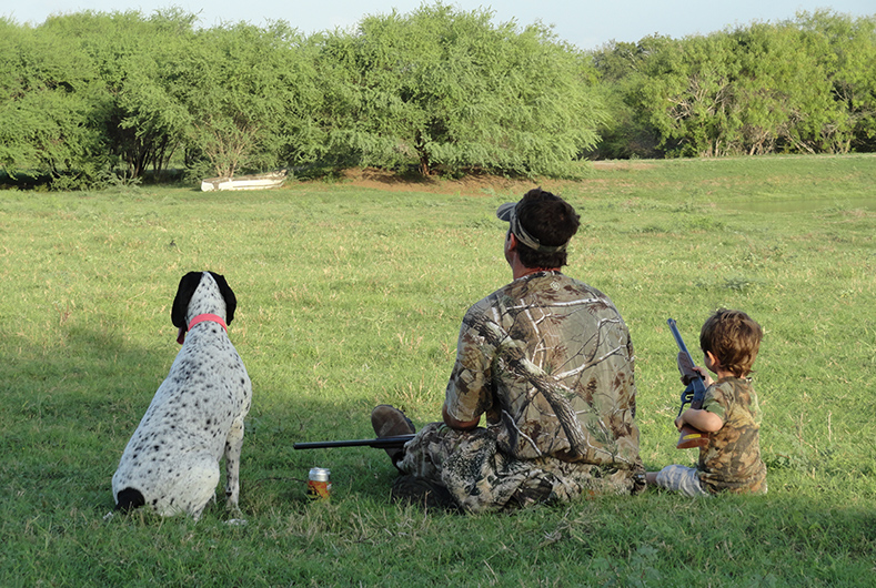 father, son and dog bird hunting
