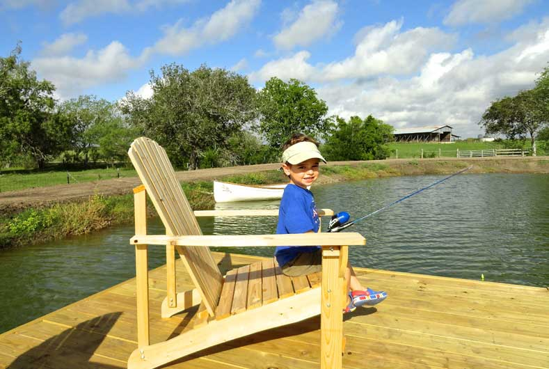 little girl sitting on big chair with fishing pole by lake