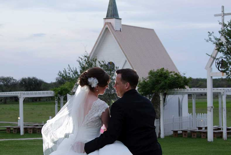 bride and groom sitting by chapel