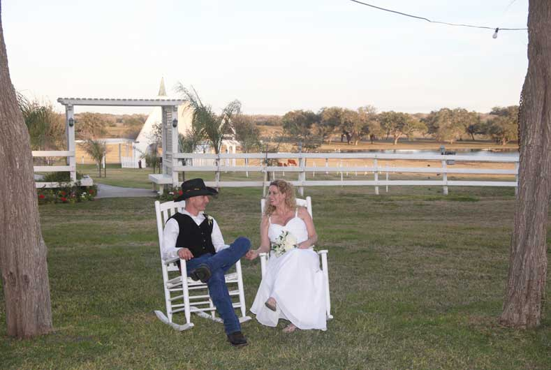 bridal couple sitting on white rocking chairs with chapel in the background