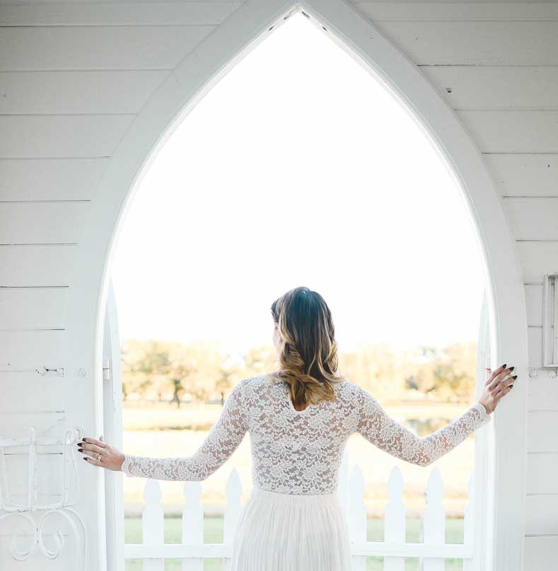 bride looking out of the chapel archway