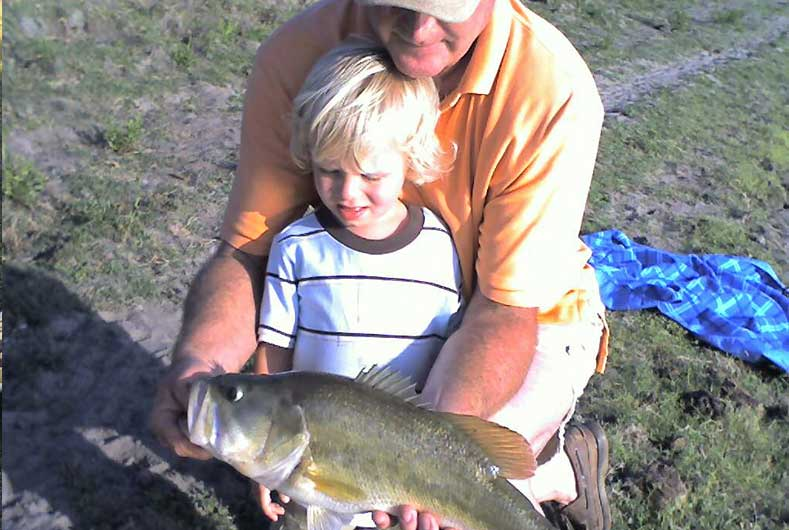 Father and son holding a large fish they caught