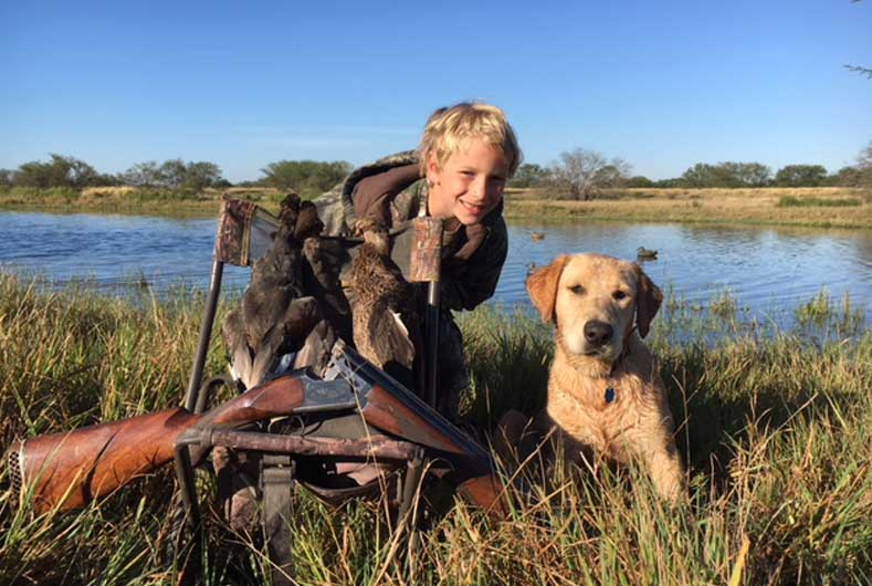 young boy hunting pictured with gun and bird dog
