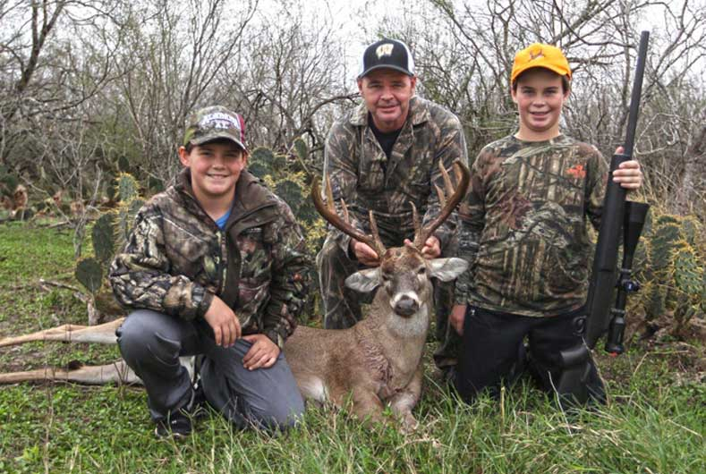 father and two sons hunting pictured with deer