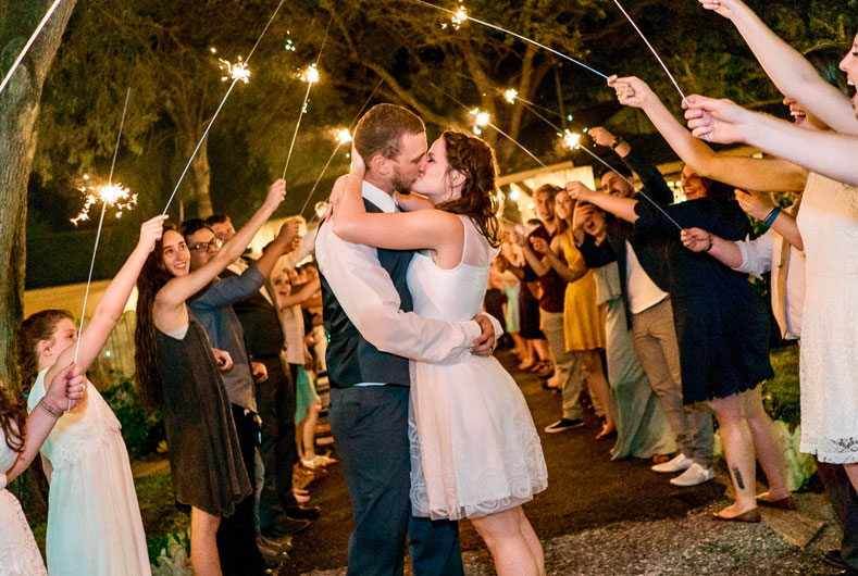 couple kissing under large sparklers held by their guests in an archway