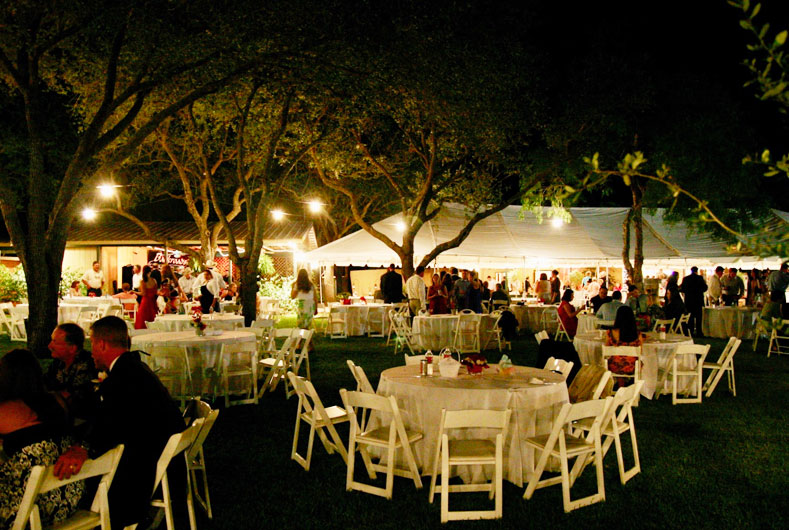 outdoor wedding reception with decorated tables and chairs in the evening